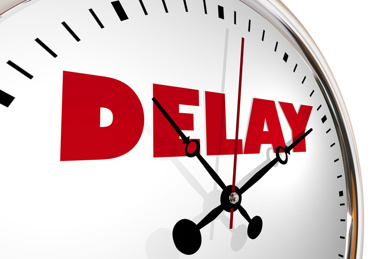"Word ""delay"" written on a clock in red."