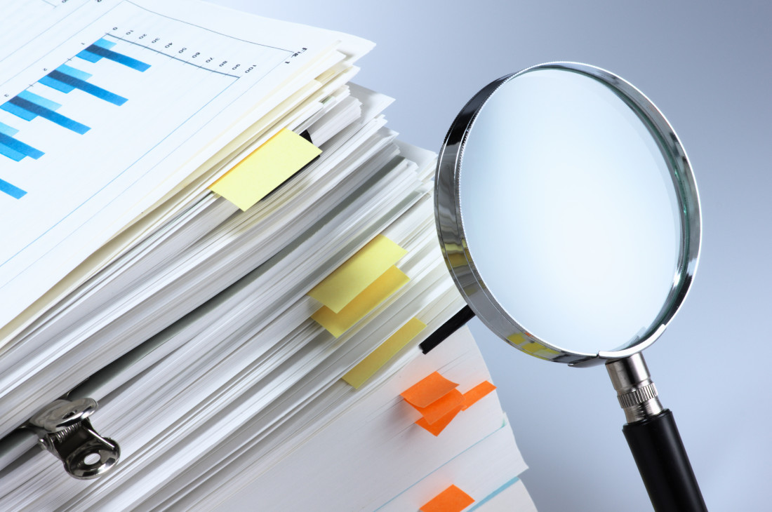 Stack of papers with magnifying glass