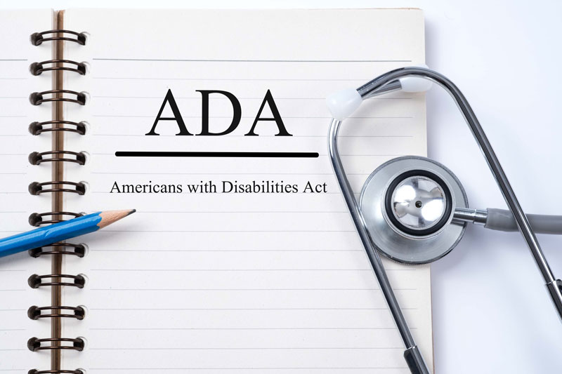 """ADA, Americans with Disabilities Act"" written on a piece of paper with a pencil and stethoscope on top."