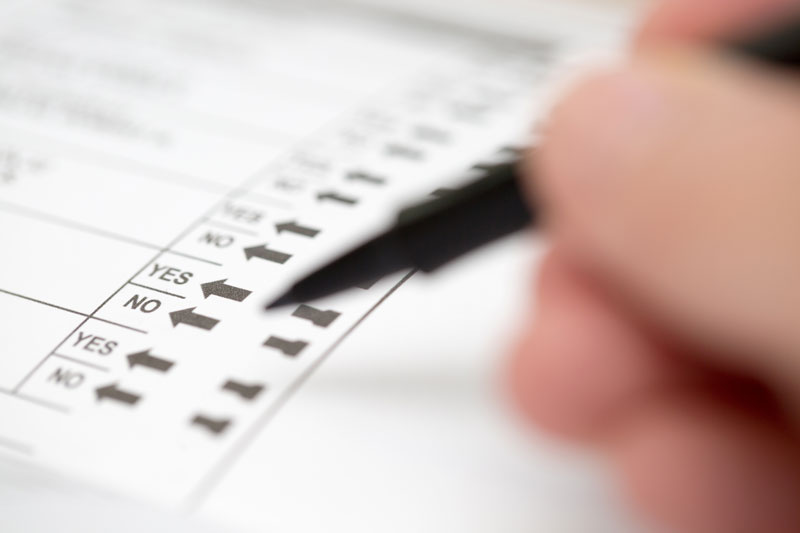 Image of a ballot with someone deciding between yes or no.