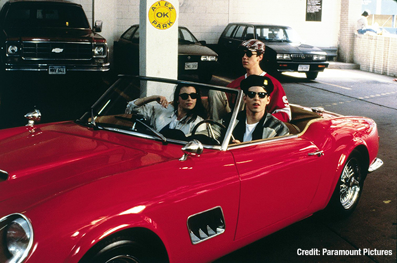 Cast of Ferris Bueller sitting in the red Ferrari from the movie