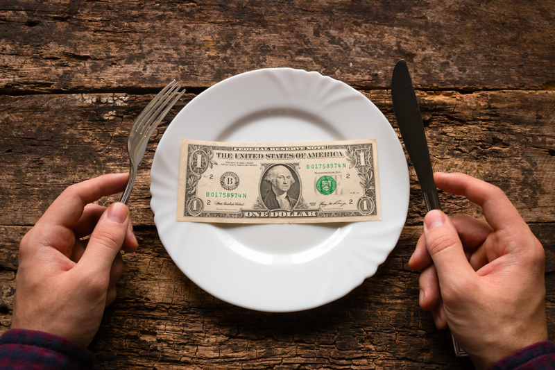 Man holding fork and knife with a plate of money