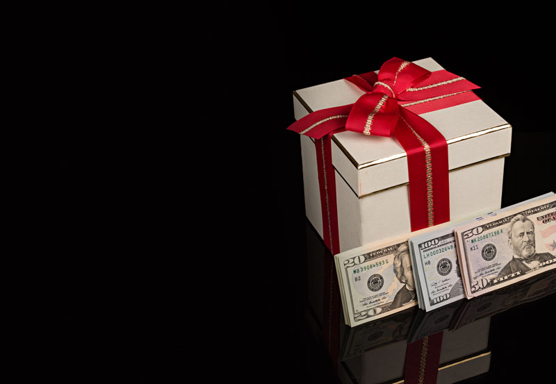 Money laying next to a gift box.