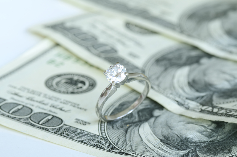 $100 bills with wedding ring on top