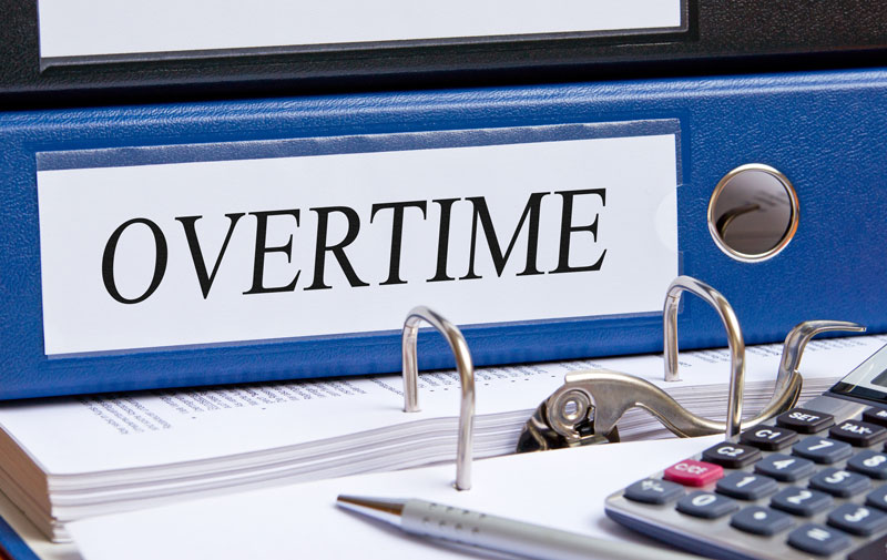 "Blue binder with the word ""overtime"" on the side, on top of a desk"