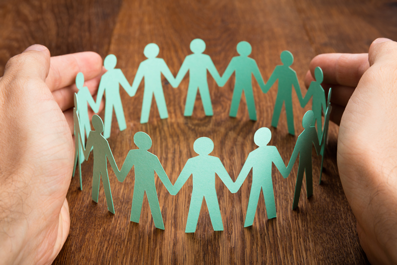 Hands protecting group of cardboard cut-out figures