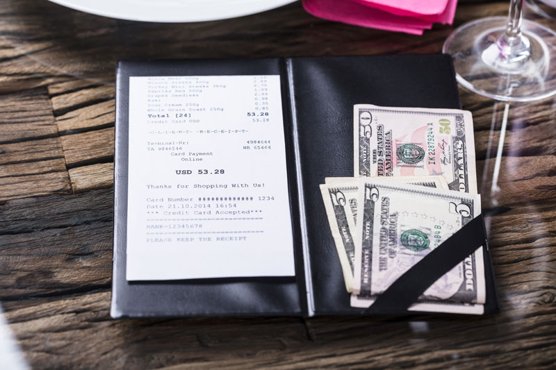 Elevated view of a restaurant bill and money, showing a tip.