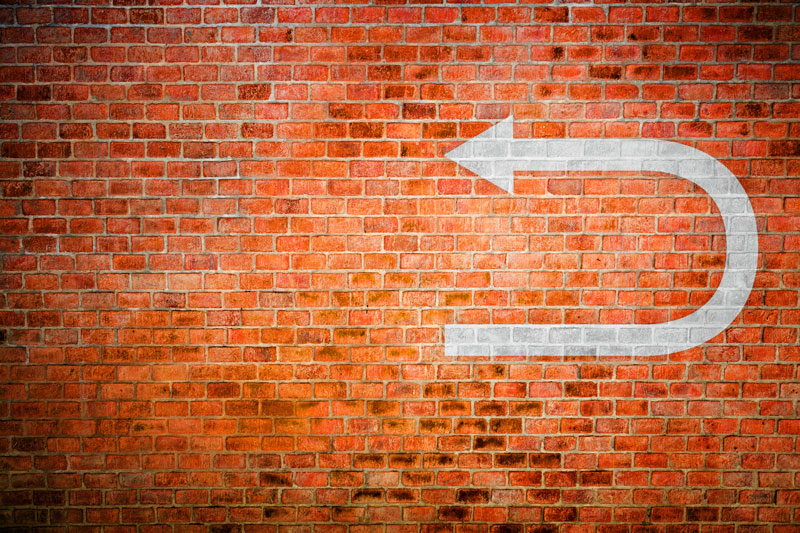 White turnaround arrow on a brick wall, showing a reversal in a decision.