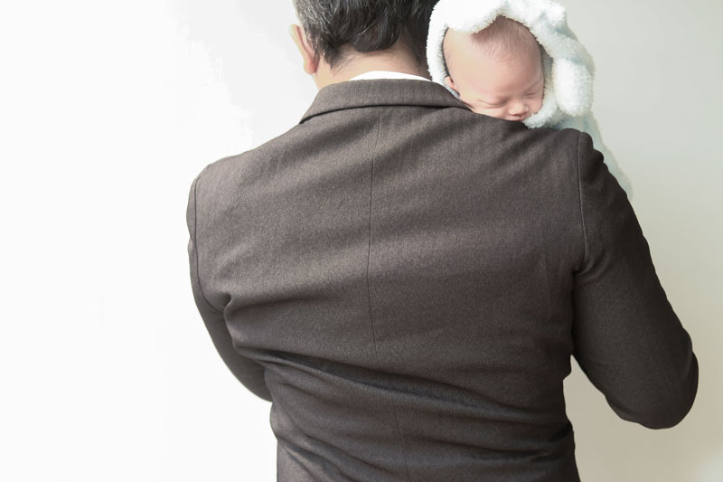 Businessman holding a baby.