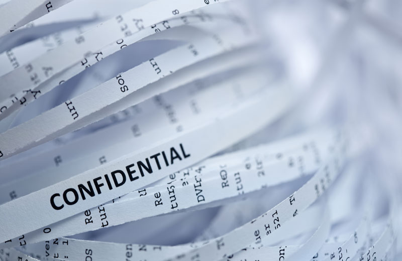 "Word ""confidential"" written on shredded paper"