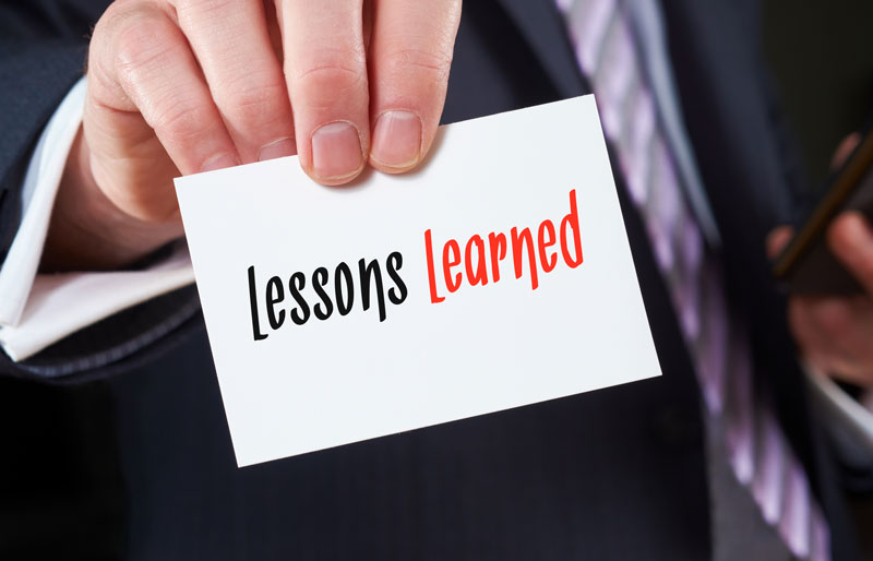 "Businessperson holding a white piece of paper that says ""Lessons Learned."""