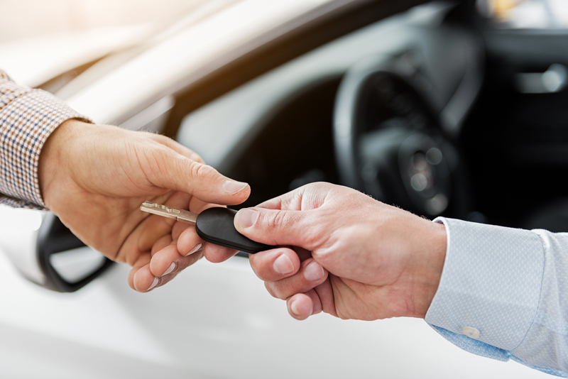 Person receiving car keys from a car salesman