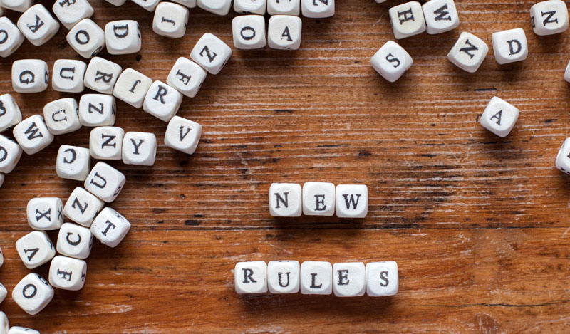 "Words ""new rules"" spelled out with blocks on a wooden table"