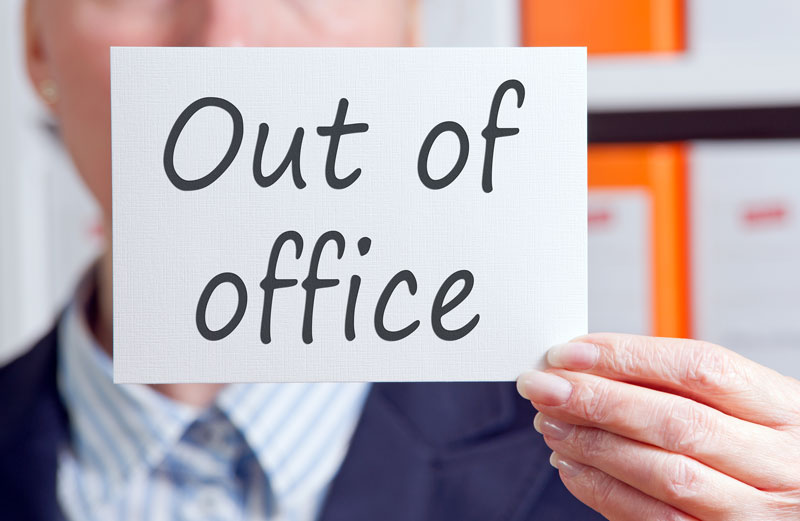 "Words ""Out of Office"" written on a piece of paper held up by a businesswoman"