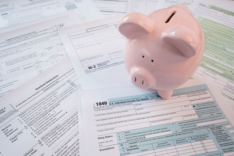 Piggy bank sitting on top of a pile of tax return papers