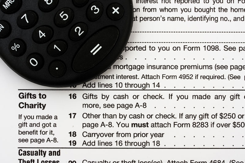 Calculator on top of a tax return, focused on the charitable giving portion of the form.