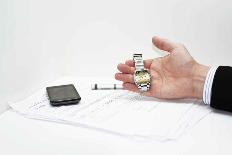 Man holding a watch on top of a stack of papers, showing time passing