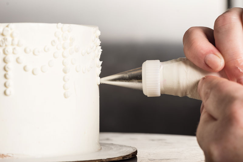 Person decorating a white wedding cake