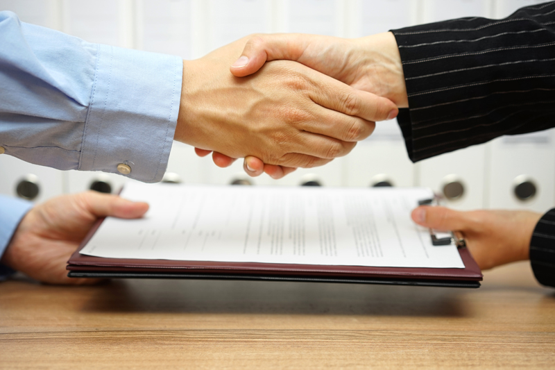 Business partners shaking hands and exchanging paperwork