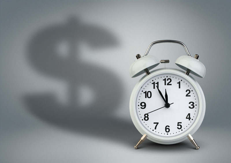 Clock with the shadow of a dollar sign, representing overtime