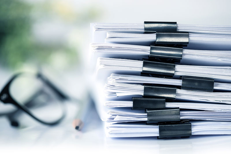 Stack of documents with a pair of glasses sitting next to them