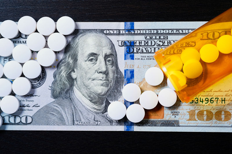 White pills spilling from medicine bottle on to US currency
