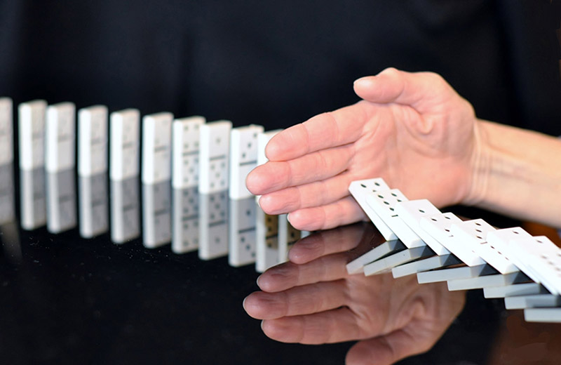 Hand stopping domino line from falling